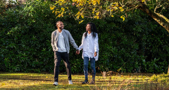 Ken and Mary Okoroafor walking outside in a park surrounded by trees and grass