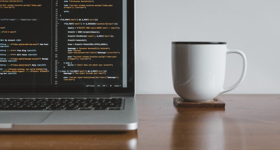 Laptop screen with coding with cup of coffee next to it