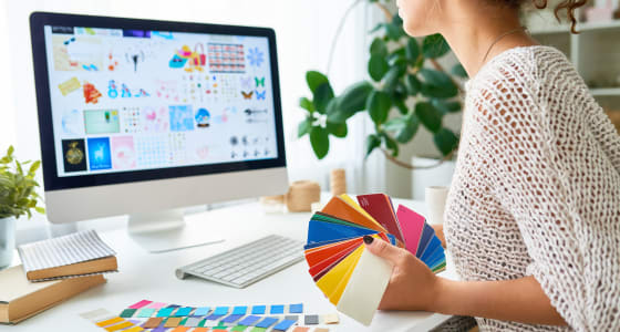 Young lady in a white jumper, working from home, looks at her computer screen while holding a bunch of colour samples