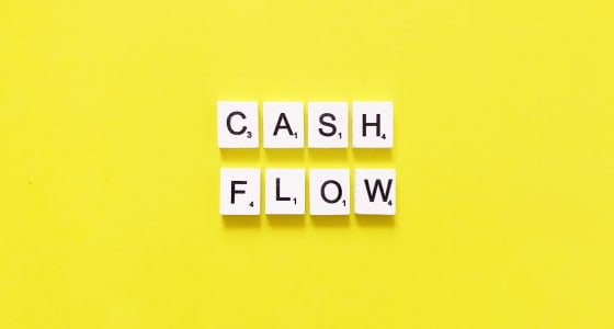 scrabble tiles that spell out cash flow on a yellow background.