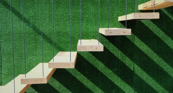 7 wooden steps suspended in front of a green astroturf background