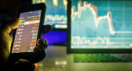 Daytrader in dark using mobile phone and screens with charts