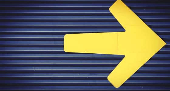 Arrow pointing right in yellow paint on a grey mental shutter