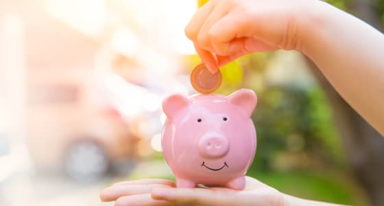 Coin being placed into a pink piggy bank with a bright but blurred background