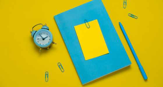 Blue notepad, pen and alarmclock on a plain yellow background