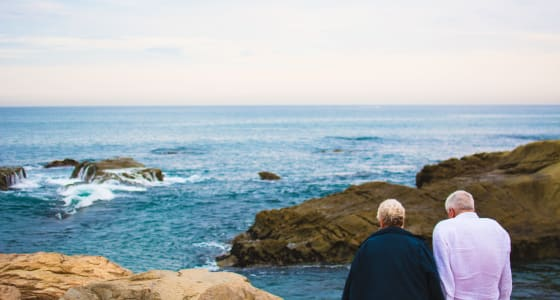 Old couple sitting infront of a cliff edge looking over the sea
