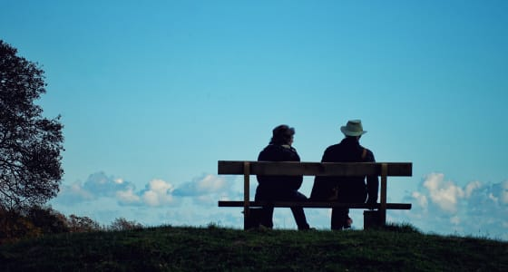 A couple sitting on a bench facing away from the viewer win a countryside setting with blue skies