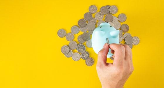 A hand places money into a piggy bank