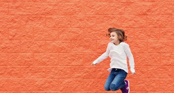 Little girl jumping in front of orange brick wall