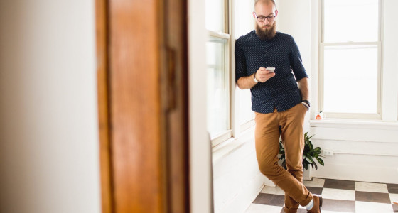 hipster man with beard and brogues standing in a hallway checking his phone