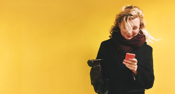 Woman looking at her phone, dressed in dark clothing standing in front of a yellow background.