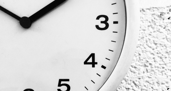 White clock, with black numbers and black hands, on a white wall