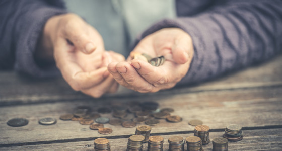 Pair of elderly hands holding some coins