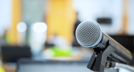 Microphone on a stand on an empty stage in a room with yellow walls