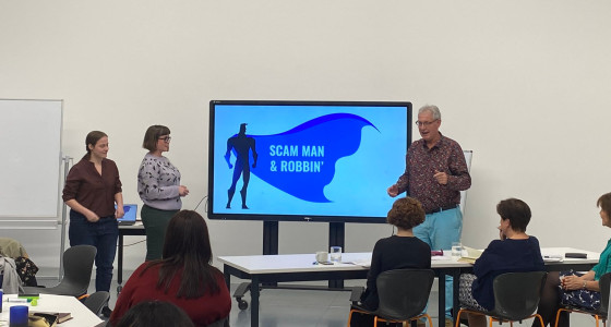 Creators of the Scam Man and Robbin presenting their game infront of whiteboard