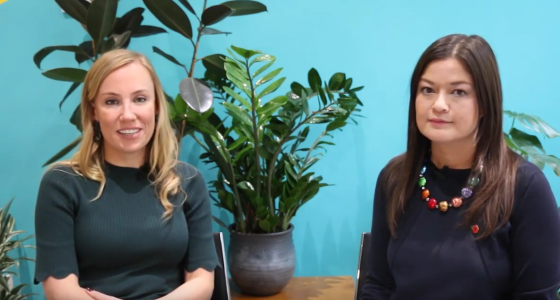 Clare Reilly from PensionBee and Nanvy Kilpatrick from Legal & General sit infront of a turquoise and yellow wall, surrounded by plants.
