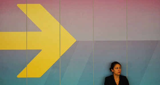 businesswoman sitting against a big yellow arrow in the background.