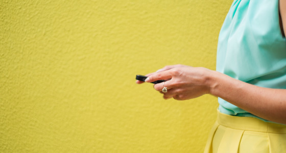 Woman in yellow skirt and blue top holding a phone infront of a yellow wall