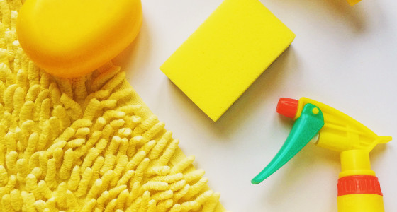 Yellow mat with yellow soap, spray and sponge on top
