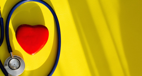 yellow background with red love heart and stethoscope
