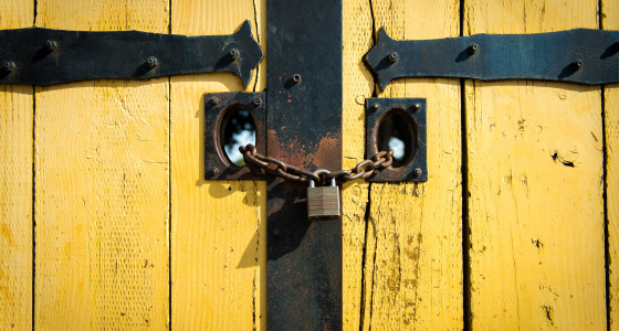 Yellow wooden panelled doors with a locked padlock and chain.