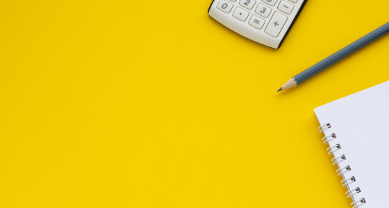 a calculator, pencil and white notepad on a yellow background