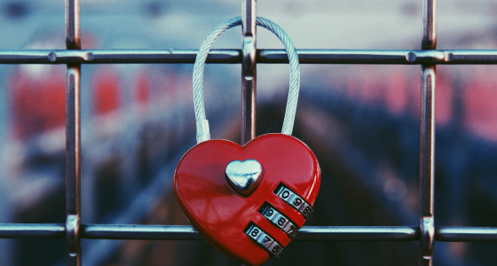 Red heart shaped lock attached to a wire fence