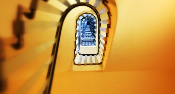 yellow spiral staircase with a black railing.