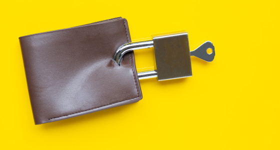 Brown wallet with padlock attached infront of a yellow background