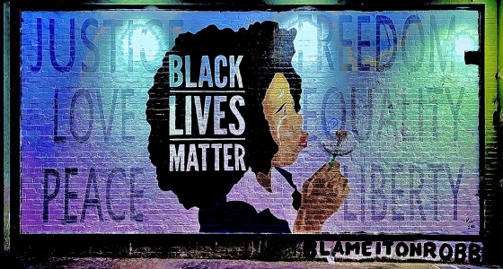 Black Lives Matter spelt out on a graffiti wall with an illustration of a black woman