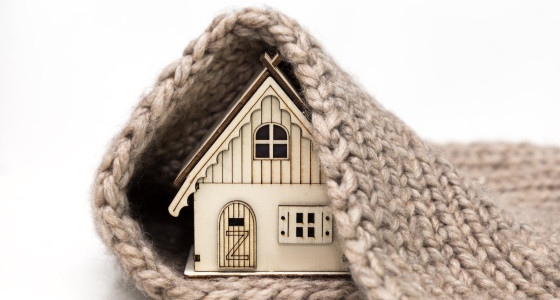 A toy house covered by a grey blanket