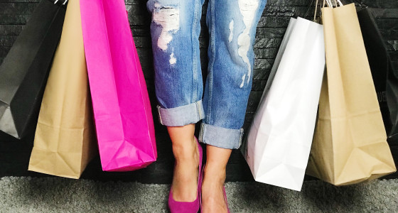 Woman in pink high-heeled shoes with multiple shopping bags
