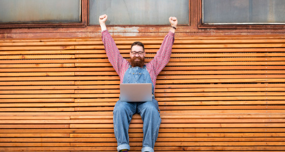 Man raising in his hands in celebration sat over a laptop