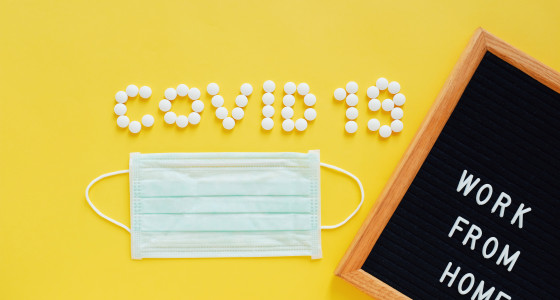 Pills that spell out 'covid 19' next to sign that reads 'work from home' and a mask.