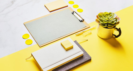 Desktop with a clipboard and office supplies on top.