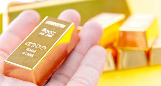 A hand holding a gold ingot