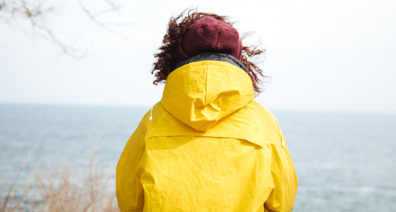 Woman in yellow coat looking out at sea.