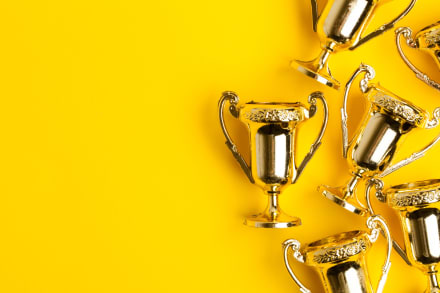 Gold trophies on a yellow background