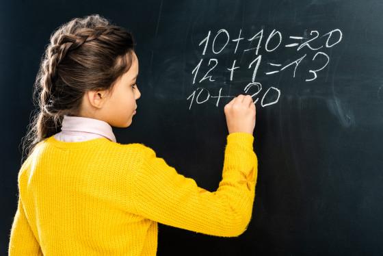 A schoolgirl in yellow jumper writing on a blackboard.