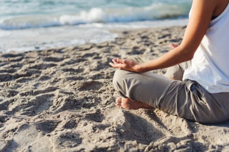 Lady sitting on sandy beach meditating in front of breaking waves