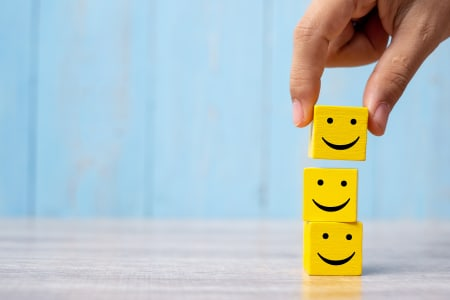 A stack of 3 yellow blocks with a smiley face on infront of a blue background
