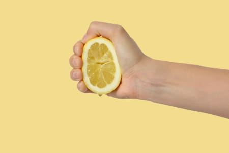 Hand squeezing a lemon