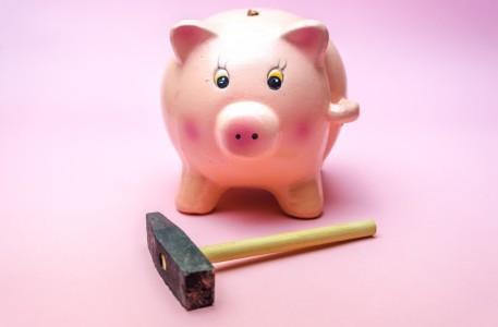 A hammer sits next to a piggy bank