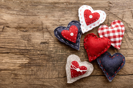 Three patchwork hearts on wooden board.