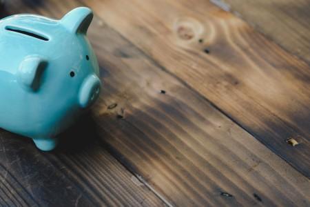 Blue piggy bank on a dark brown wooden floor