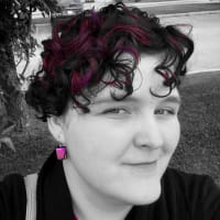 Black and white photo of a woman with pops of pink in her hair and on her earrings.