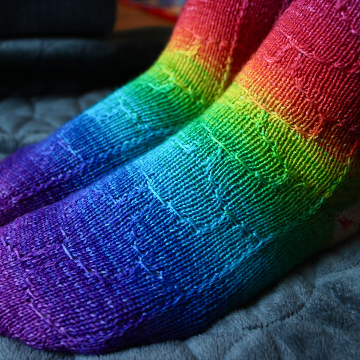 Side view of rainbow socks with subtle surface detail.