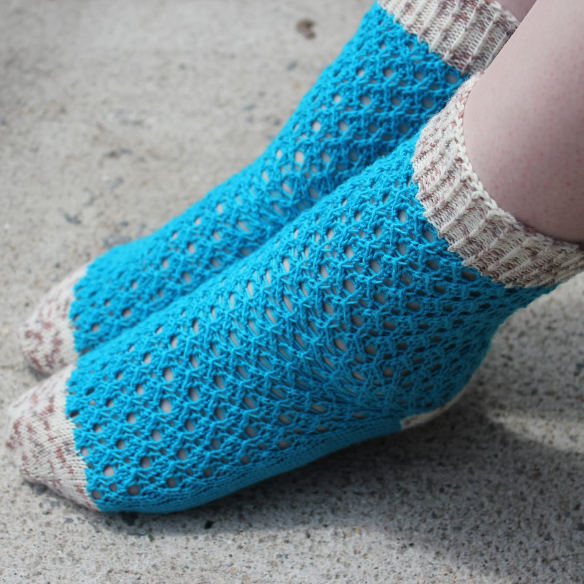 Top view of feet with pointed toes wearing bright blue lace socks with white and brown speckled heels, toes, and cuffs.