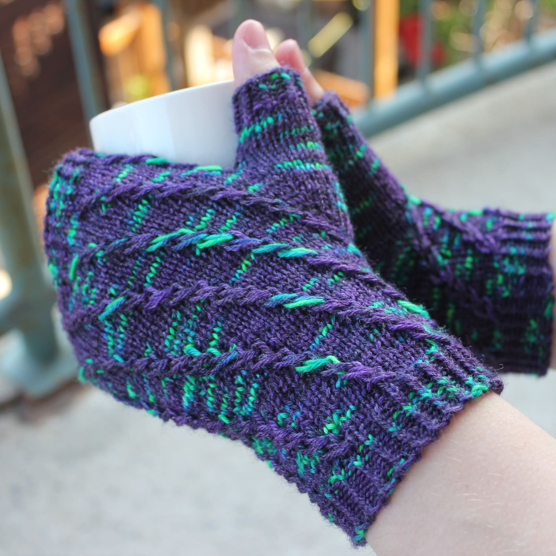 Side view of hands holding a white mug and wearing dark purple fingerless mitts with bright green flecks in a twisting spiralling pattern.