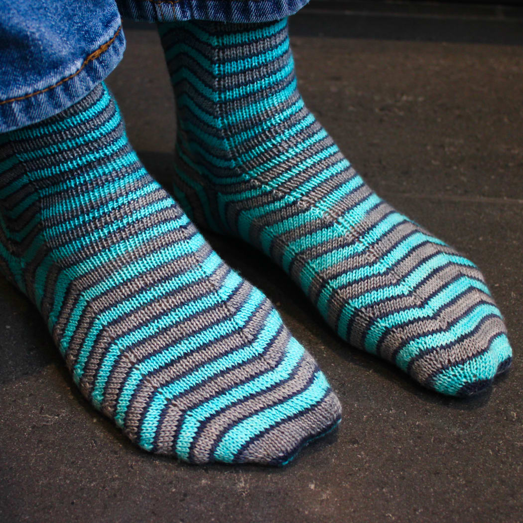 Front view of grey and blue socks with stripes that are distorted on the sides.